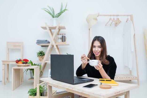 Glückliches mädchen, das auf notizbuch schreibt, schaut auf laptop-bildschirm, hört zu und lernt online-klasse zu hause