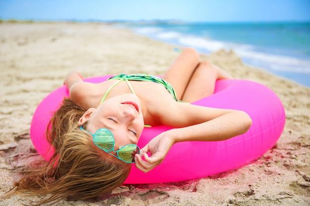 Glückliches mädchen, das auf strand ein sonnenbad nimmt.