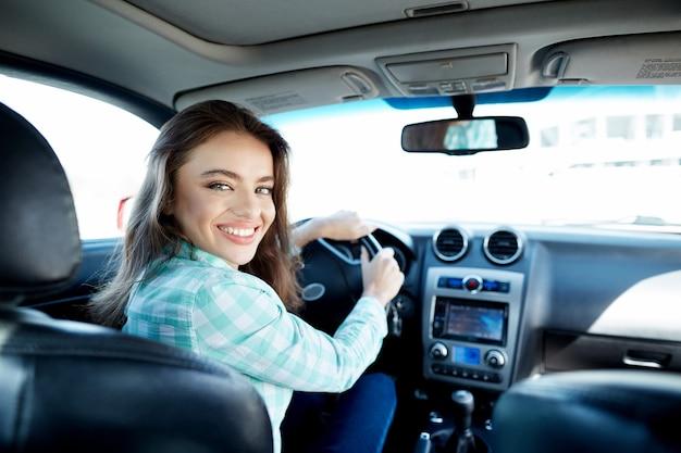 Glückliches mädchen, das blaues hemd trägt, das im neuen auto sitzt, im verkehr, im porträt feststeckt, neues auto kauft, fahrerin.