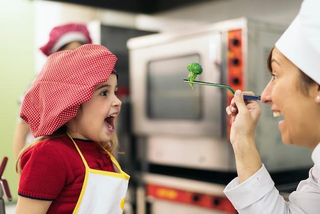 Glückliches mädchen, das brokkoli in einer küche isst.