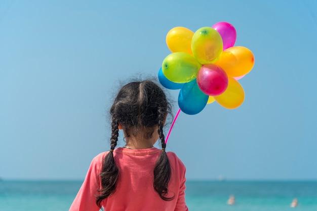 Glückliches mädchen, das bunte luftballons auf den strand-sommerzeiten hält