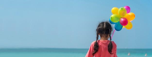 Glückliches mädchen, das bunte luftballons auf den strand-sommerzeiten mit netzfahne und leerem kopienraum hält.