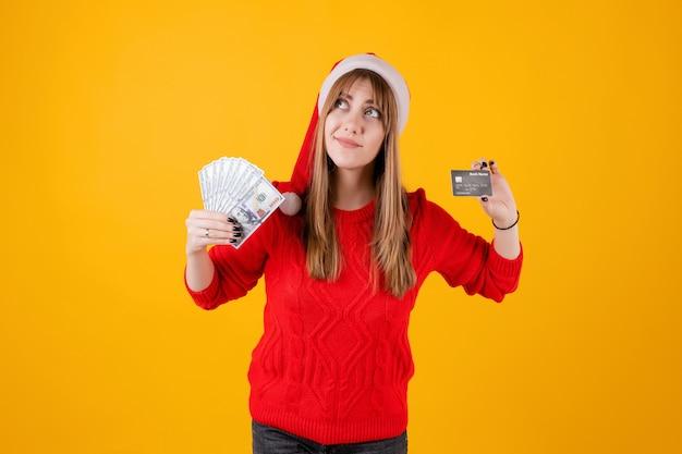 Glückliches mädchen, das das dollargeld und schablonenkreditkarte tragen sankt-hut hält