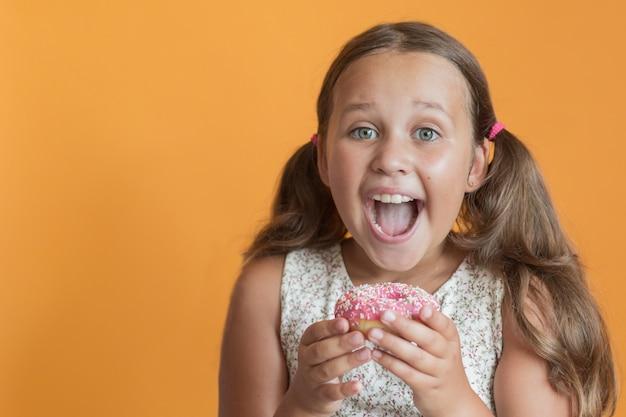 Glückliches mädchen, das donat auf orange wand isst