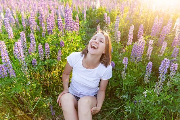Glückliches mädchen, das draußen lächelt. schöne junge brünette frau, die auf sommerfeld mit blühendem grünem blumengrüntisch ruht. kostenlose glückliche europäische frau. positiver gesichtsausdruck der menschlichen emotion.