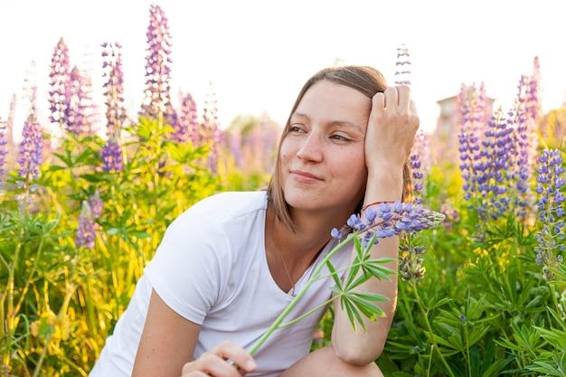 Glückliches mädchen, das draußen lächelt. schöne junge brünette frau, die auf sommerfeld mit blühenden blumen ruht. kostenlose glückliche europäische frau. positiver gesichtsausdruck der menschlichen emotion.