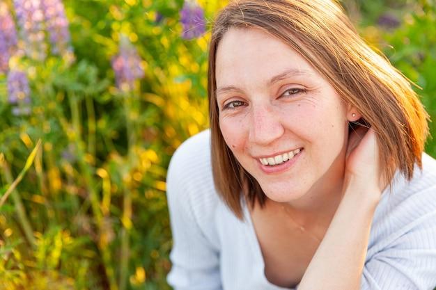 Glückliches mädchen, das draußen lächelt. schöne junge brünette frau, die auf sommerfeld mit blühenden wilden blumen ruht. kostenlose glückliche europäische frau. positiver gesichtsausdruck der menschlichen emotion.