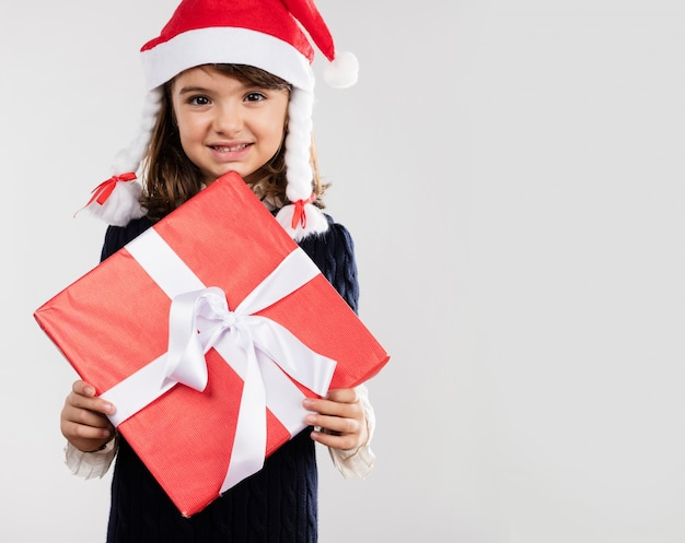 Glückliches mädchen, das ein geschenk mit weißem band halten