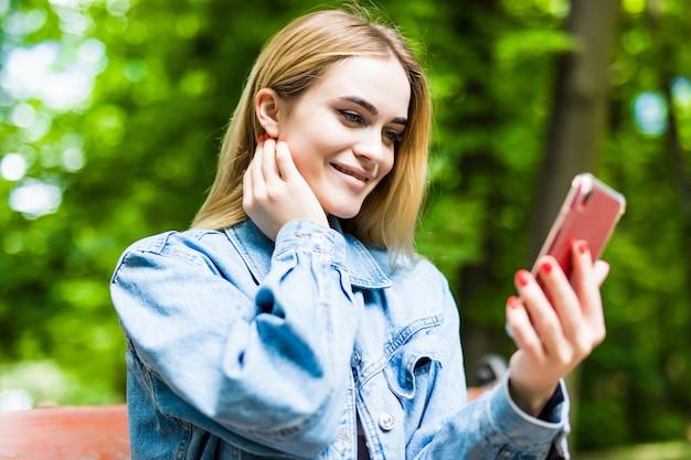 Glückliches mädchen, das ein telefon in einem stadtpark benutzt, der auf einer bank sitzt