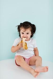 Glückliches mädchen, das eine banane isst