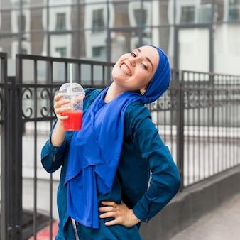 Glückliches mädchen, das einen hijab trägt und einen smoothie hält