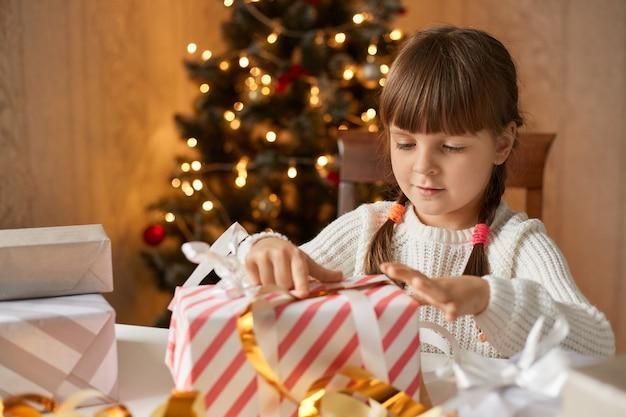 Glückliches mädchen, das geschenkbox beim sitzen am tisch öffnet