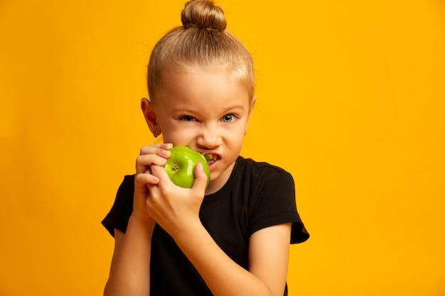 Glückliches mädchen, das grünen apfel, frischen apfel der hübschen mädchenstücke der nahaufnahme lokalisiert auf einem gelben hintergrund isst. gesunder lebensstil und essen. früchte und gemüse. gesundes zahnkonzept