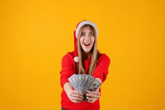 Glückliches mädchen, das hundert dollarscheine in der hand trägt sankt-hut hält