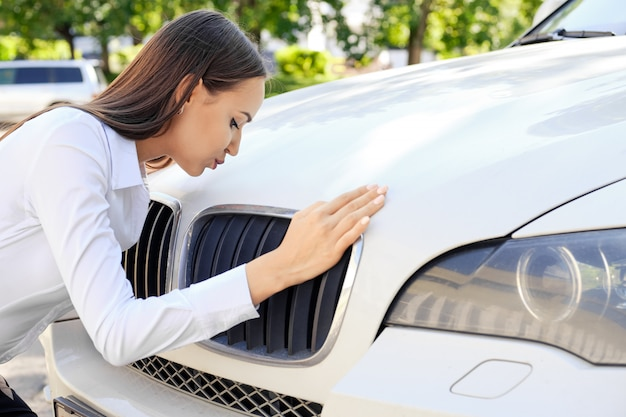 Glückliches mädchen, das ihr auto küsst