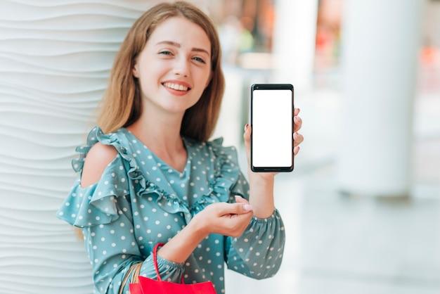 Glückliches mädchen, das ihr telefon zeigt
