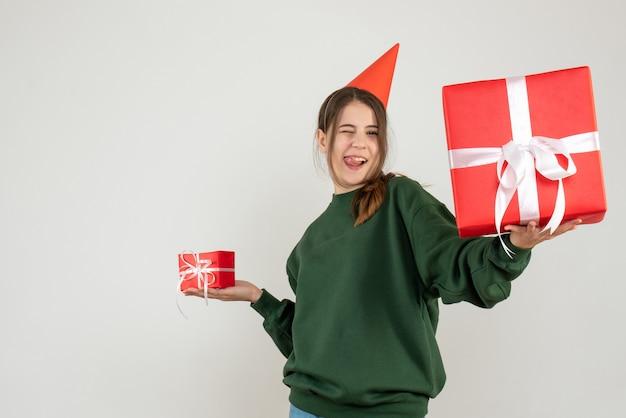 Glückliches mädchen, das ihr weihnachtsgeschenk betrachtet, das ihre zunge auf weiß zeigt