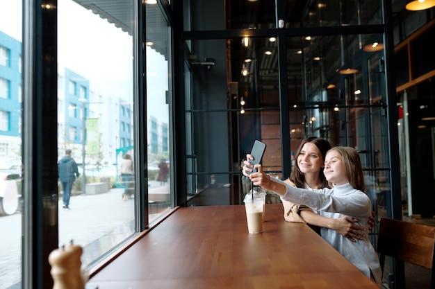 Glückliches mädchen, das ihre arme mit smartphone ausdehnt, während selfie mit mutter im café durch fenster macht