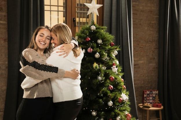 Glückliches mädchen, das ihre mutter für weihnachten umarmt