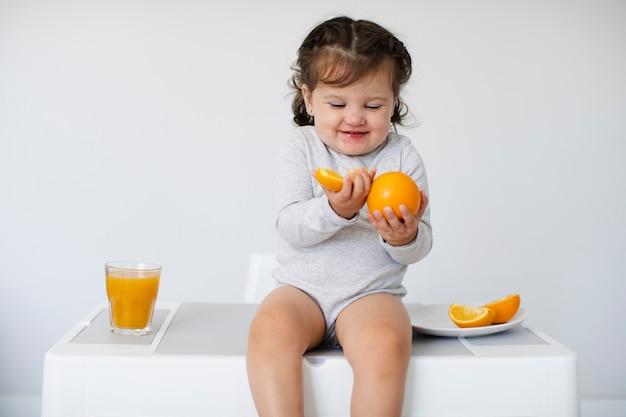 Glückliches mädchen, das ihre orangen betrachtet