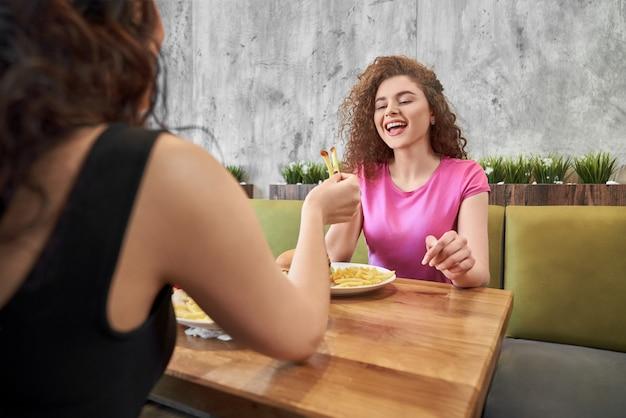 Glückliches mädchen, das im café mit freund sitzt und pommes frites isst.