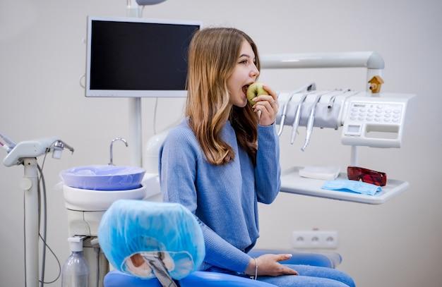 Glückliches mädchen, das im zahnarztstuhl sitzt und frischen apfel nach erfolgreicher zahnbehandlung isst