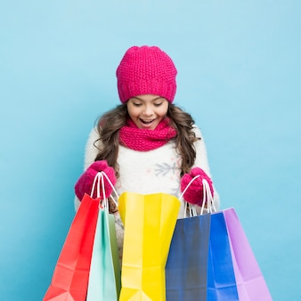 Glückliches mädchen, das in den einkaufstaschen schaut Kostenlose Fotos