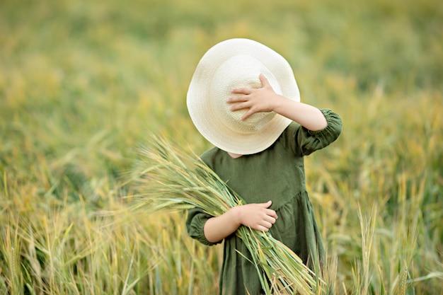 Glückliches mädchen, das in den goldenen weizen, das leben auf dem gebiet genießend geht. naturschönheit und weizenfeld. familienleben im freien. freiheitskonzept. nettes kleines mädchen auf dem sommergebiet