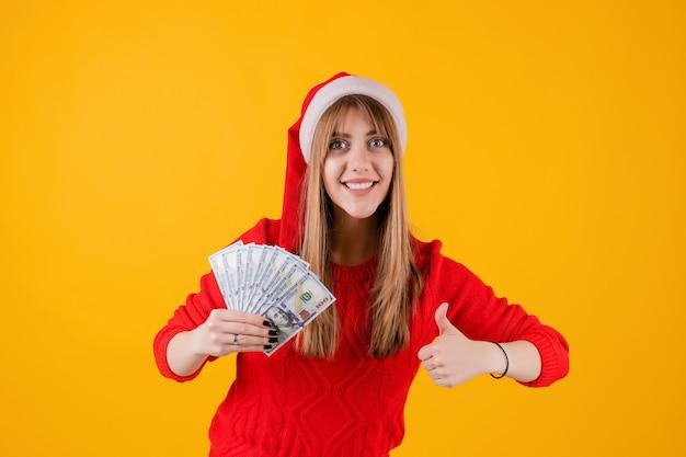 Glückliches mädchen, das in der hand geld hält und den daumen trägt sankt-hut oben zeigt