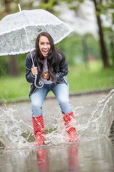Glückliches mädchen, das in regenstiefeln in pfützen springt, lacht und einen regenschirm über sich hält.