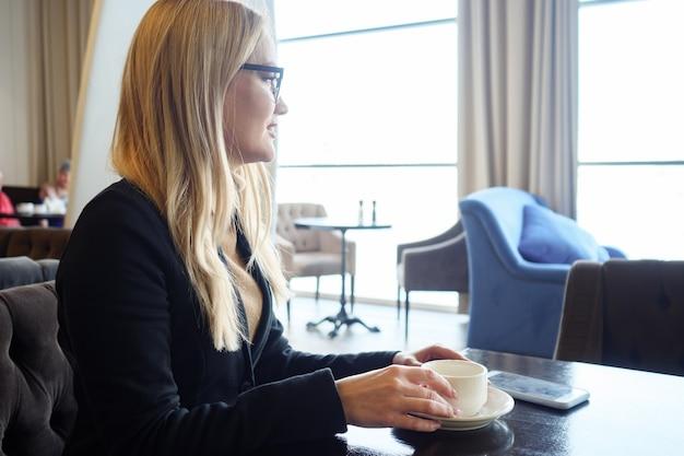 Glückliches mädchen, das kaffee trinkt, sich im café entspannt und auf das fenster schaut