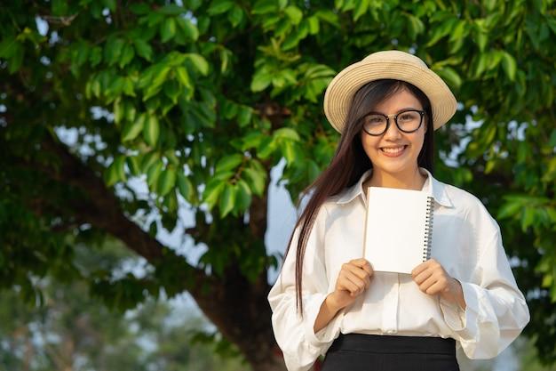 Glückliches mädchen, das leeres notizbuch mit natur hält