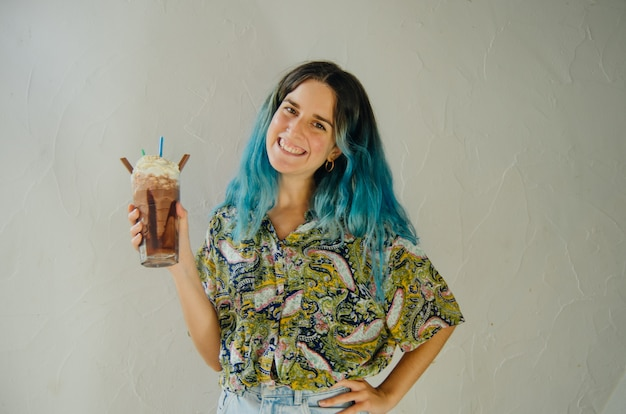 Glückliches mädchen, das mit einem großen schokoladenmilchshake in einem kaffeegeschäft lächelt