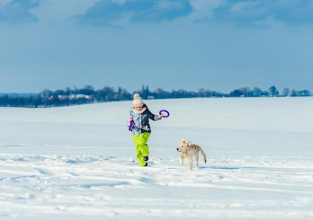 Glückliches mädchen, das mit niedlichem hund im funkelnden schnee läuft