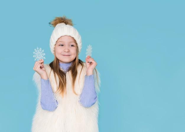 Glückliches mädchen, das mit schneeflocken spielt