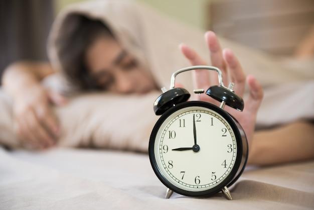 Glückliches mädchen, das morgens aufwacht, den wecker in ihrem schlafzimmer abstellend.