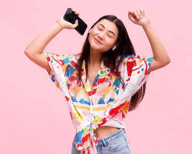 Glückliches mädchen, das musik auf smartphone hört
