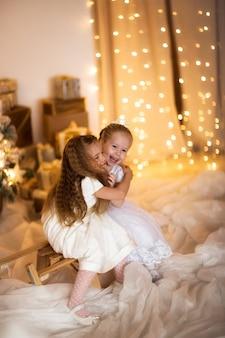 Glückliches mädchen, das nahe dem weihnachtsbaumkonzept frohen weihnachten spielt