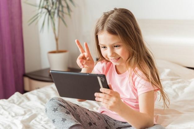 Glückliches mädchen, das online zu hause auf dem bett plaudert