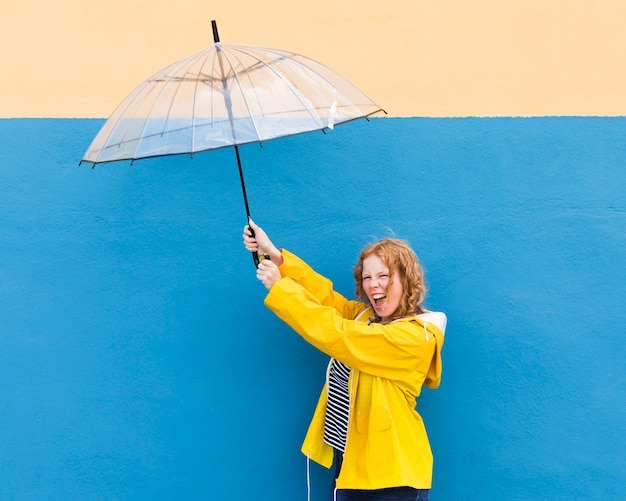 Glückliches mädchen, das regenschirm hält