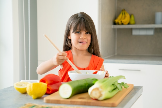 Glückliches mädchen, das salat in schüssel mit großem holzlöffel wirft. entzückendes kind, das lernt, gemüse zum abendessen zu kochen, posiert, zunge herausstreckt. kochkonzept lernen