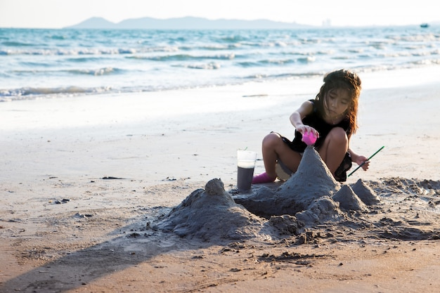 Glückliches mädchen, das sand auf dem strand im sommer spielt