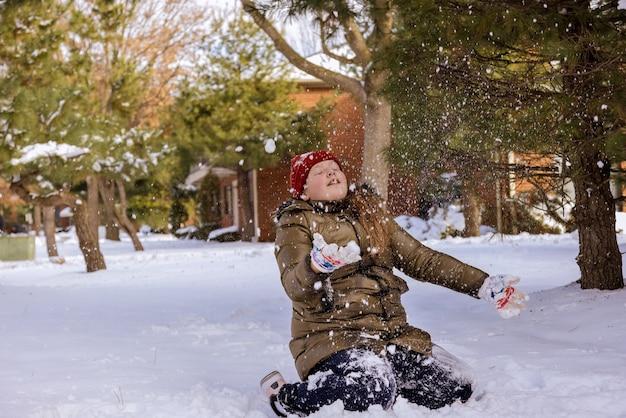Glückliches mädchen, das schönen wintertag im freien genießt und mit schnee zur winterzeit spielt