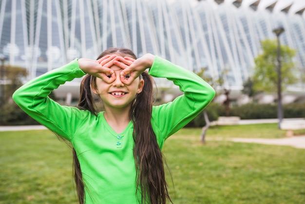Glückliches mädchen, das schutzbrille mit ihrem finger steht im park bildet
