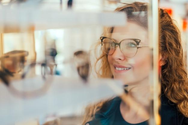 Glückliches mädchen, das sich entscheidet, neue gläser zu kaufen.