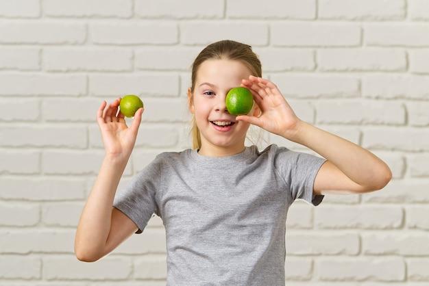 Glückliches mädchen, das spaß hat und ihre augen mit limette, gesunder ernährung, bio-lebensmittel, fruchtdiät, konzept bedeckt