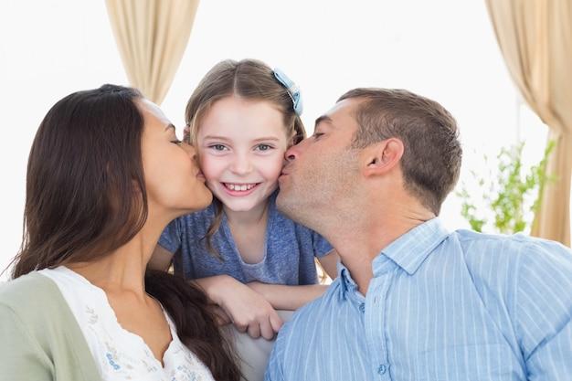 Glückliches mädchen, das von den eltern geküsst wird