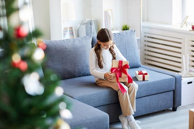 Glückliches mädchen, das weihnachtsgeschenke öffnet