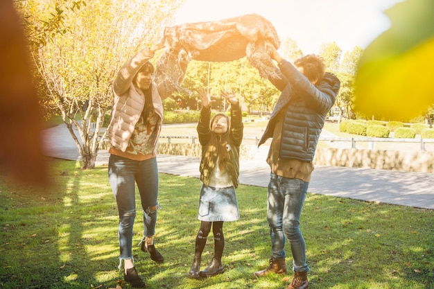 Glückliches mädchen, das wochenende mit ihren eltern im park genießt