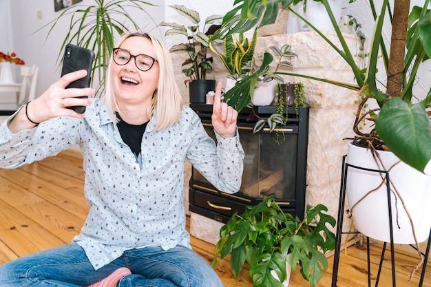 Glückliches mädchen, das zu hause küche sitzt und videoanruf hält. junge frau, die smartphone für videoanruf mit freund oder familie verwendet. vlogger-aufnahme-webinar. frau, die kamera schaut und grußhände winkt